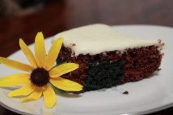 A slice of brown and green swirl red velvet cake with lemon buttercream icing alongside a yellow daisy.