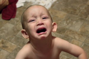 A toddler crying with mouth agape